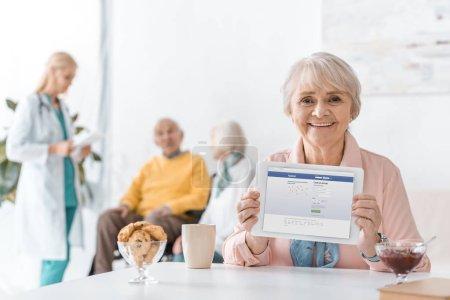 senior woman showing facebook app on digital tablet screen at nursing home