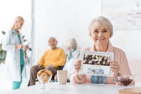 Photo pour Hauts femme montrant depositphotos app sur l'écran de la tablette numérique à la maison de soins infirmiers - image libre de droit
