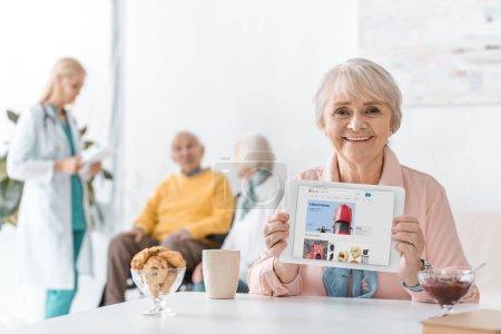 Photo for Senior woman showing ebay app on digital tablet screen at nursing home - Royalty Free Image