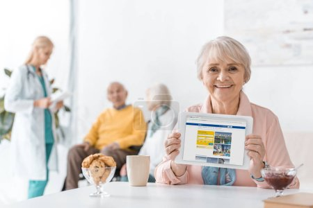 senior woman showing booking app on digital tablet screen at nursing home