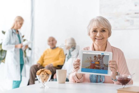 senior woman showing couchsurfing app on digital tablet screen at nursing home