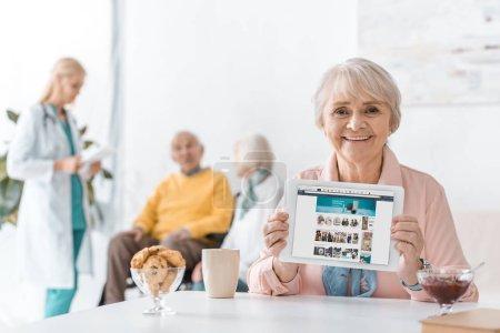 senior woman showing amazon app on digital tablet screen at nursing home