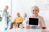 senior woman showing black screen on digital tablet at hospital