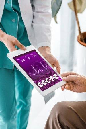 close up on doctor and patient hands holding digital tablet with cardiogram on screen