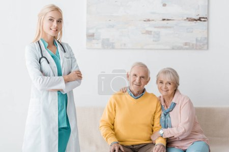 female doctor standing near senior smiling patients in clinic