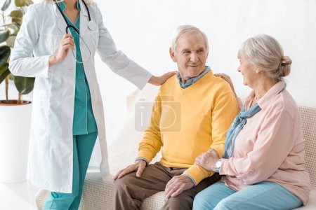 female doctor standing near senior patients in clinic