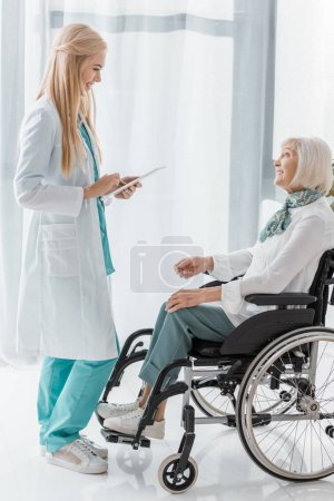 young female doctor writing prescription on clipboard to disabled senior woman