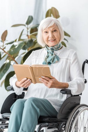 Photo for Happy senior woman sitting in wheelchair and reading book - Royalty Free Image