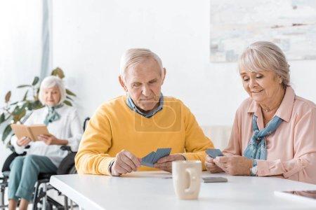cartes à jouer patients âgés à table en clinique