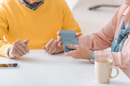 close up of senior people playing cards on white table