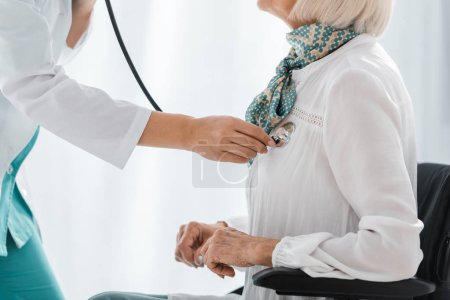 close up of young female doctor examining with stethoscope disabled senior woman
