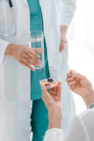 close up of young female doctor giving pills and glass of water to senior woman