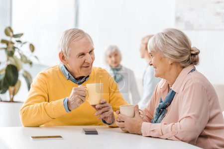 souriant, senior homme et le femme boire thé à table en clinique