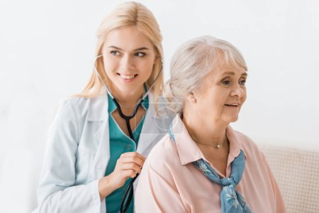 young smiling female doctor examining with stethoscope senior woman