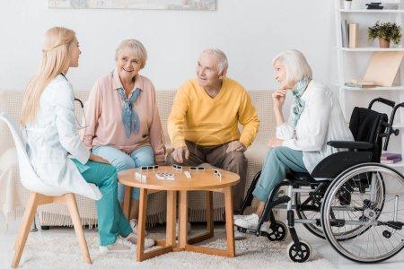 jeune infirmière jouer domino avec les patients âgés