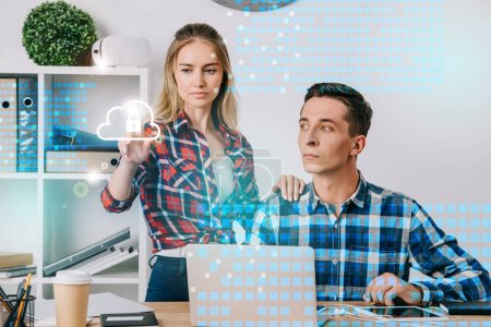businessman looking at female colleague pointing at cyber security sign at workplace in office, web security concept