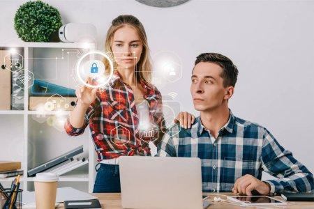 businessman looking at female colleague pointing at cyber security signs at workplace in office, web security concept