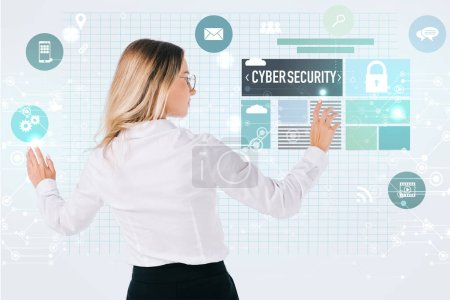 back view of businesswoman in eyeglasses pointing at cyber security signs isolated on white, information security concept