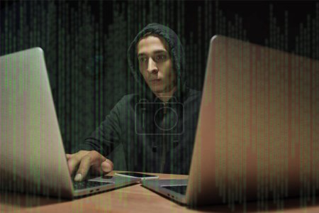 portrait of hacker in black hoodie using laptops at tabletop with smartphone, cyber security concept