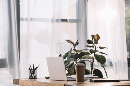 Photo pour Bouchent la vue du lieu de travail avec ordinateur portable, le café pour aller et portable - image libre de droit