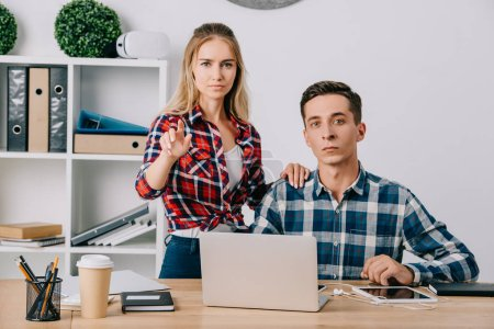 businessman looking at female colleague gesturing at workplace in office