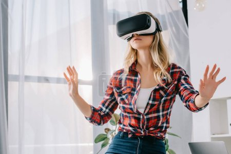 young woman in virtual reality headset gesturing in room