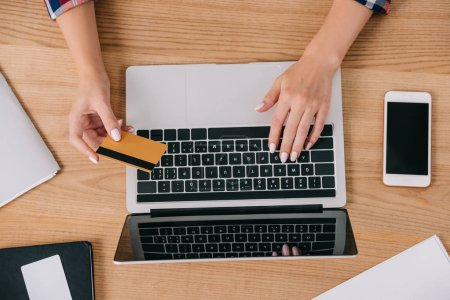 partial view of woman with credit card making purchase online at wooden tabletop