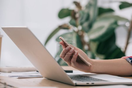 cropped shot of businesswoman with smartphone at workplace with laptop