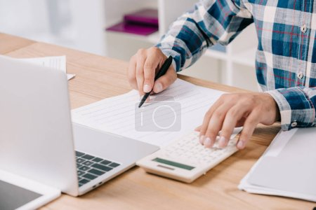 partial view of businessman making calculations at workplace with documents and laptop