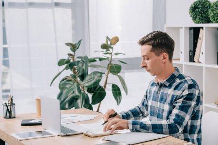 Foto de Vista lateral del empresario enfocado haciendo cálculos en lugar de trabajo con documentos y portátil en la oficina - Imagen libre de derechos