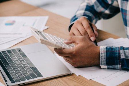 Photo pour Recadrée tir d'homme d'affaires avec calculateur travaillant sur les lieux de travail avec des documents et ordinateur portable - image libre de droit