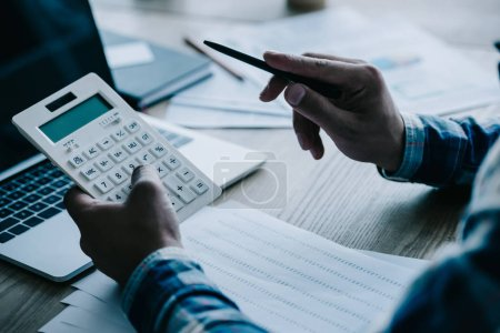Photo for Cropped shot of businessman with calculator working at workplace with documents and laptop - Royalty Free Image