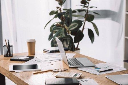 Photo pour Vue rapprochée du lieu de travail avec ordinateur portable, table, documents et café à emporter - image libre de droit