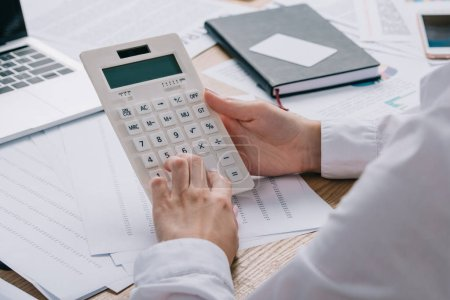 Photo for Cropped shot of businesswoman making calculations on calculator at workplace with documents - Royalty Free Image