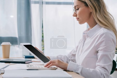 side view of focused businesswoman with tablet making calculations on calculator at workplace with papers in office
