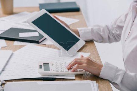Photo pour Recadrée tir de femme d'affaires avec tablette, faire des calculs sur calculatrice sur lieu de travail avec des papiers de bureau - image libre de droit