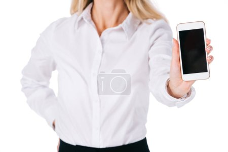 partial view of businesswoman showing smartphone with blank screen isolated on white
