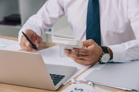 Photo pour Recadrée tir d'homme d'affaires, faire des calculs sur lieu de travail avec les papiers et ordinateur portable - image libre de droit