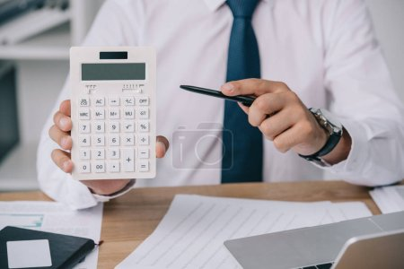 partial view of businessman pointing at calculator in hand at workplace, accounting concept