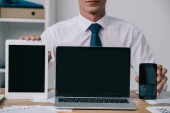 """Постер, картина, фотообои """"Обрезанный снимок бизнесмена, показаны ноутбук, планшет и смартфон с пустой экран на рабочем месте в офисе"""""""