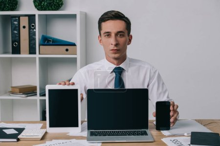 Photo for Portrait of businessman showing laptop, tablet and smartphone with blank screens at workplace in office - Royalty Free Image