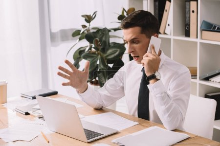 emotional businessman gesturing while having conversation on smartphone at workplace in office