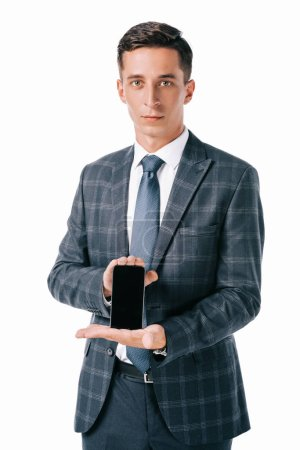 portrait of businessman in suit showing smartphone with blank screen isolated on white