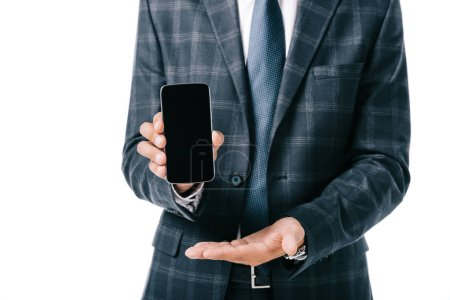 cropped shot of businessman in suit showing smartphone with blank screen isolated on white