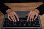 partial view of female hacker using digital laptop at wooden tabletop