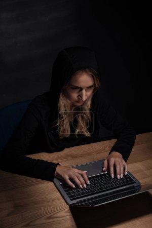 Foto de Mujer en negro con capucha usando laptop, concepto de la seguridad de cyber - Imagen libre de derechos