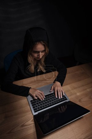 woman in black hoodie using laptop, cyber security concept