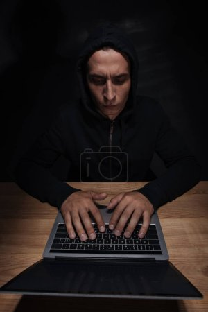 focused hacker in black hoodie using laptop at wooden tabletop, cuber security concept