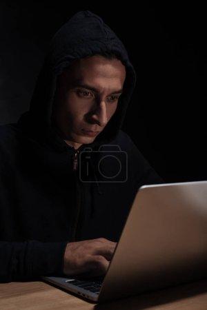 hacker in black hoodie using laptop, cuber security concept