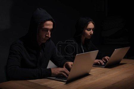 focused hackers in black hoodies using laptops in dark room, cyber security concept